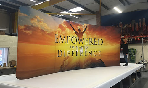 Colour Graphics Director Vicki Birch pictured with one of their 6m curve displays printed on Berger Expandable textile.